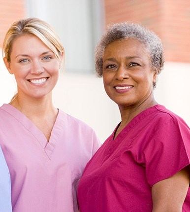 multi-generational nurses in pink scrubs
