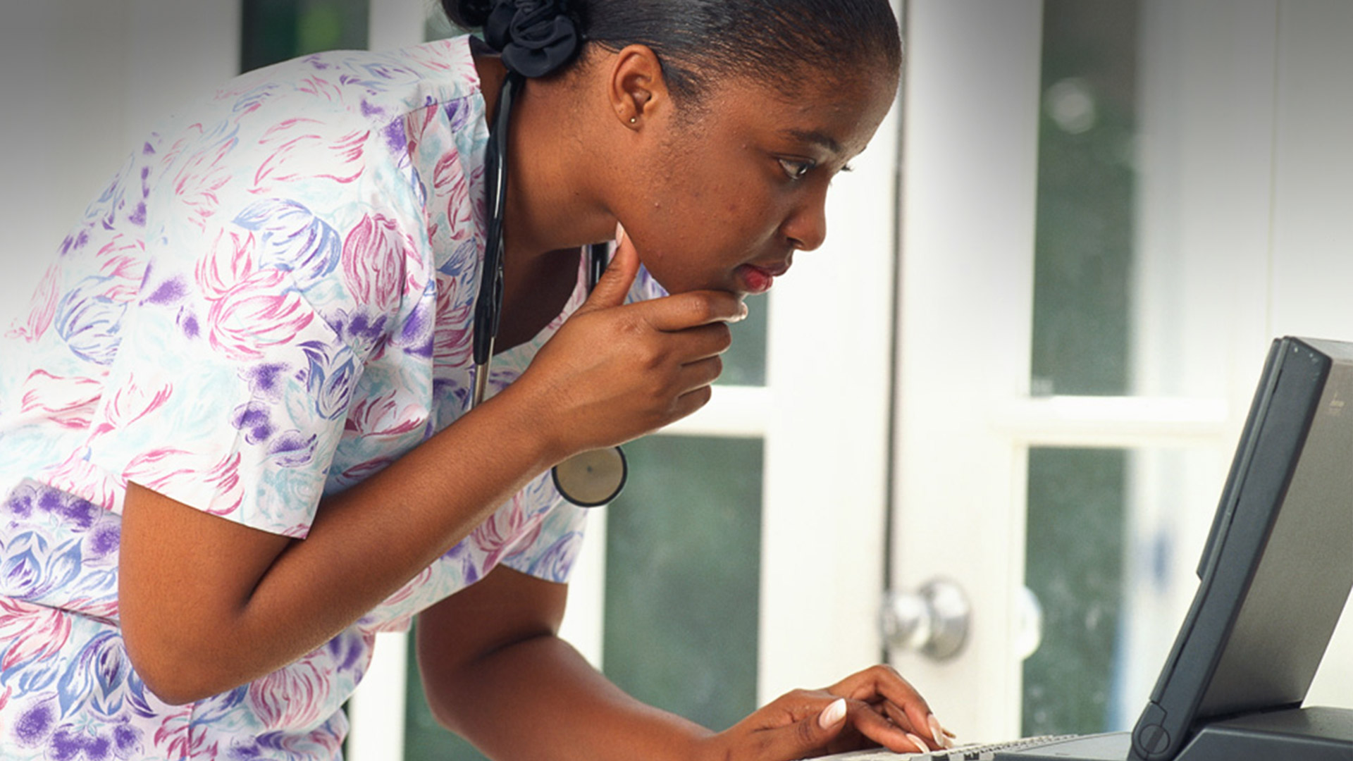 Black nurse considering all the benefits of ANA at her workstation.
