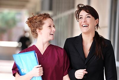Female Doctor and Nurse laughing in Hospital Corridor