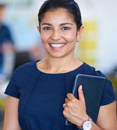 Younger nurse in business dress holding documents, smiling confidently