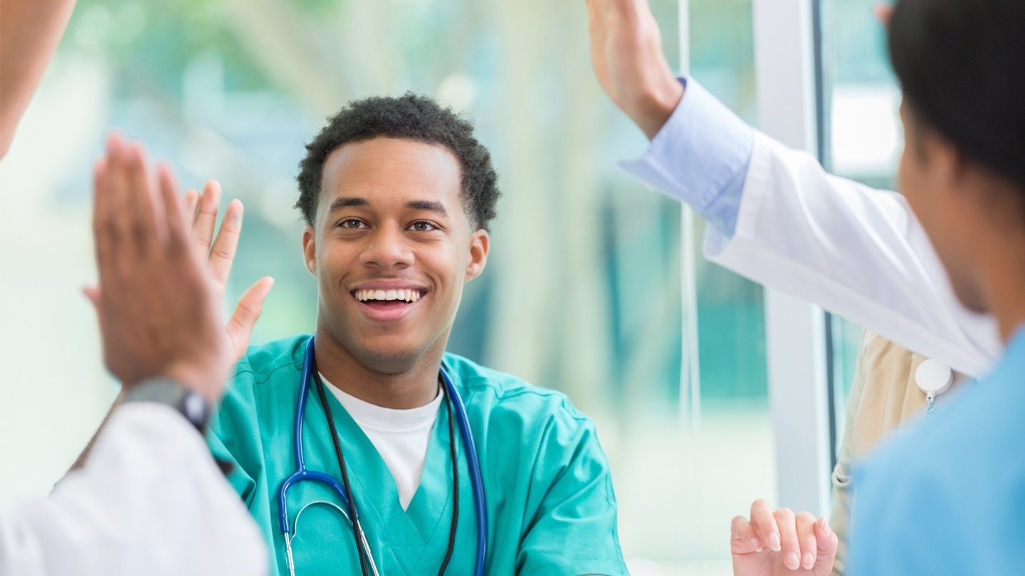 A nurse cheering with his colleagues